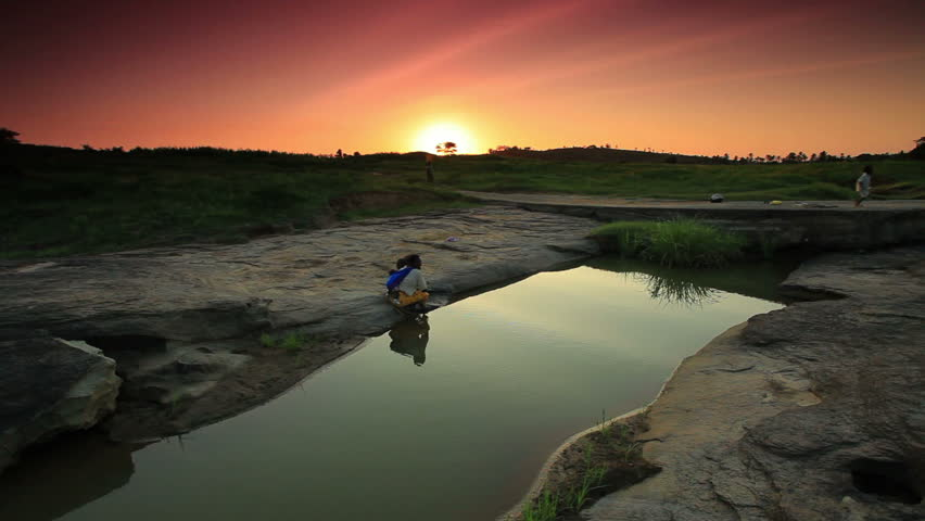 An african woman washes her child at a river near a village in Kenya two hours north of the Africa city Mombassa.