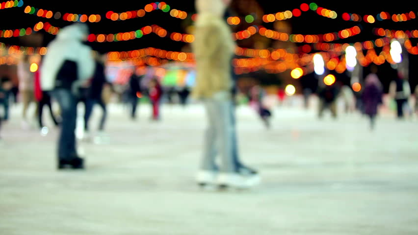 Winter outdoor ice skating with Christmas lights & crowds of people at night - HD stock footage clip