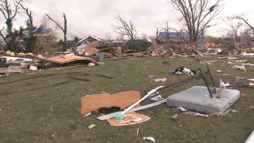 Panning across the path of destruction of a tornado, with demolished homes.