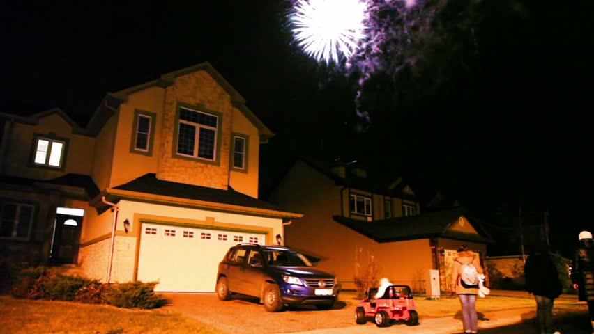 Few people watch fireworks at dark sky over house in cottage village, car stand in front of gate - HD stock video clip