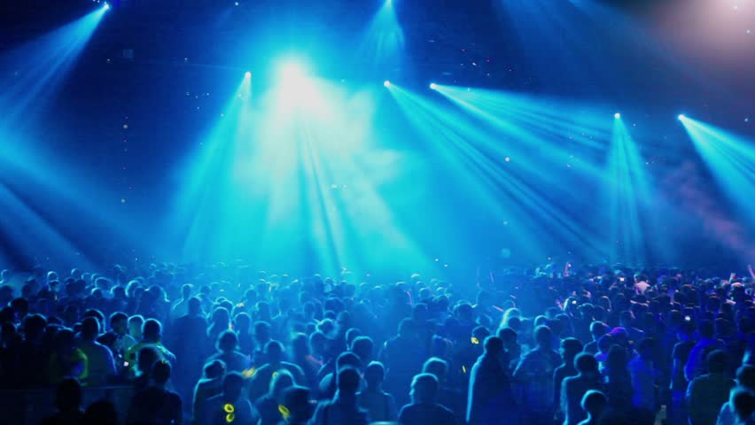Many people at rave party, crowd dance in blue light of projectors