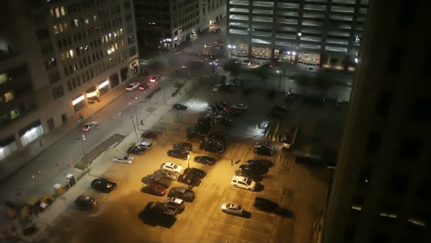 A downtown parking lot surrounded by large office buildings shows sparse nighttime activity. - HD stock video clip