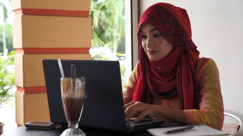 Beautiful muslim women typing on notebook - HD stock footage clip
