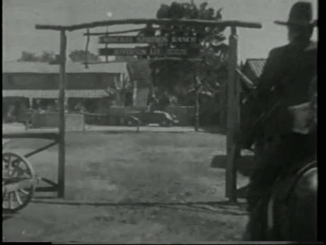 Rear view of cowboys on horseback riding into ranch
