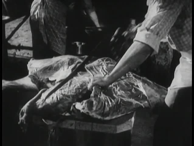 Butcher sawing carcass
