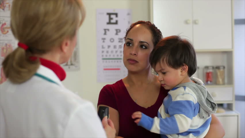 A mature Caucasian pediatrician talks to a pretty Hispanic mother about her toddlers condition. - HD stock footage clip