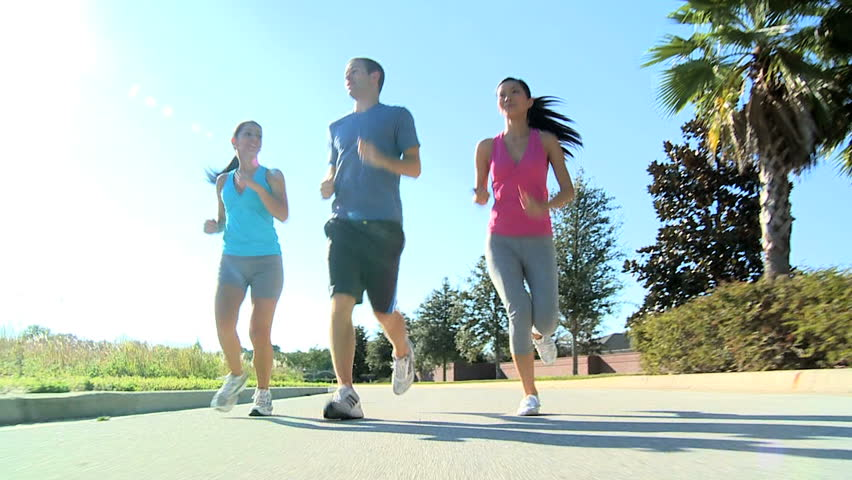 Young multi ethnic friends keeping to a fitness program together jogging outdoors - HD stock footage clip