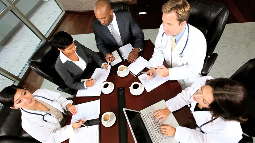 Overhead shot of young multi ethnic medical executives meeting in the boardroom of a modern hospital building