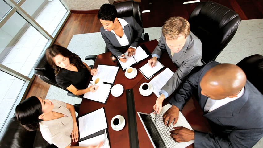 Overhead view of five multi ethnic executives in city clothes meeting in a modern office boardroom