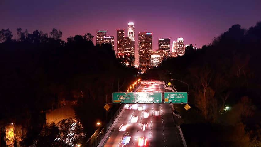 Downtown Los Angeles skyline and freeway city traffic at night. Timelapse. - HD stock video clip