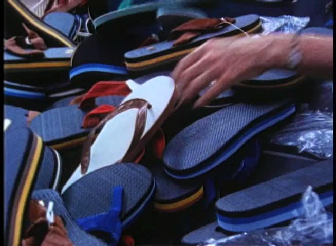 Woman looking through pile of flip flops