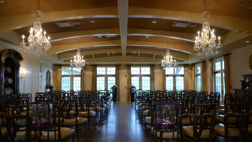 Classy and elegant wedding ceremony setup indoors with rows of empty chairs and gorgeous chandeliers