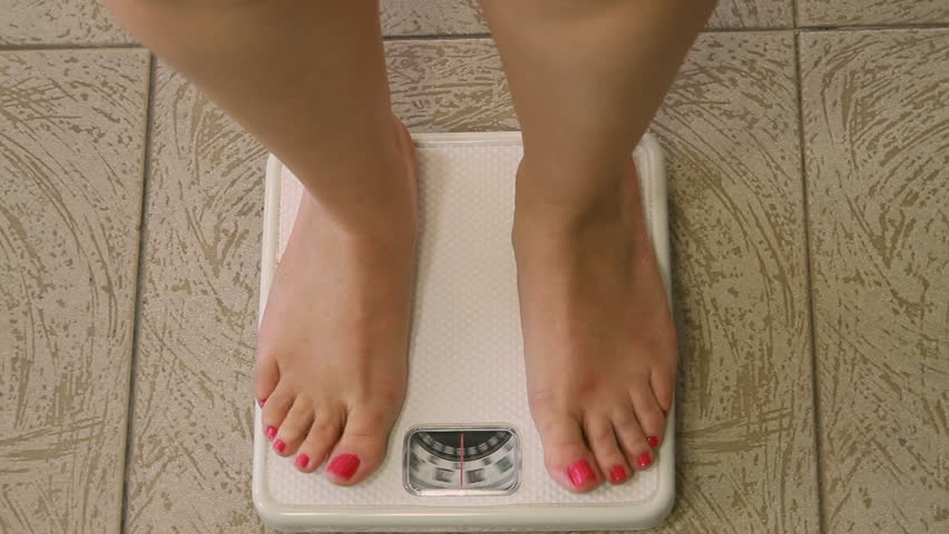 Woman on Weight Scale Sequence (HD). Sequence of shots of female legs and feet standing on a weight scale. Passing 200lbs.