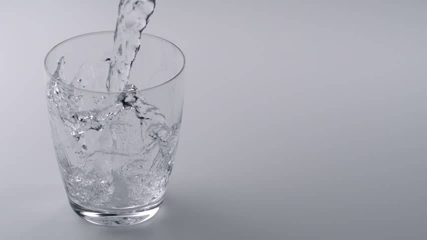Super slo-mo water falling into glass - HD stock video clip