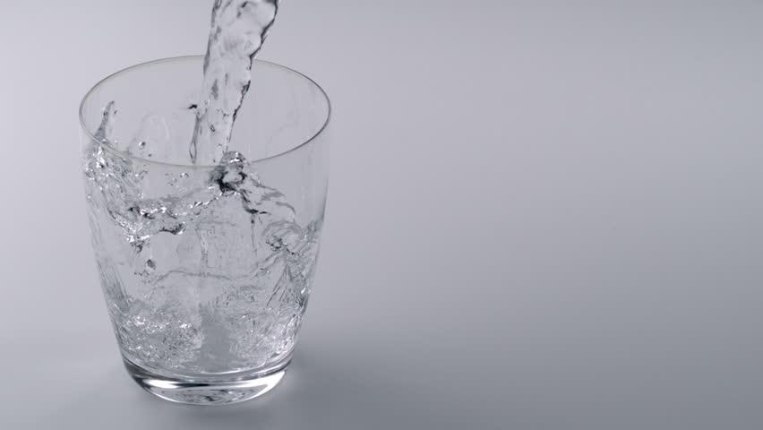 Super slo-mo water falling into glass - HD stock video clip