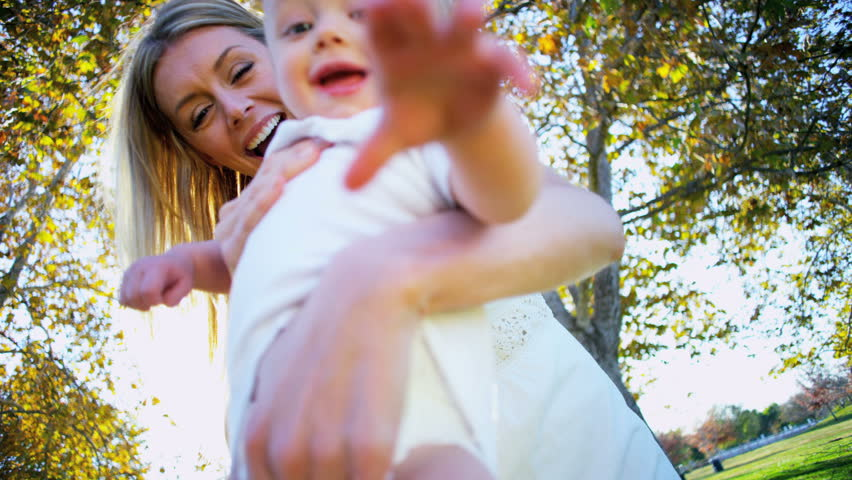 Blonde baby laughing as his beautiful young mom swings him through the air