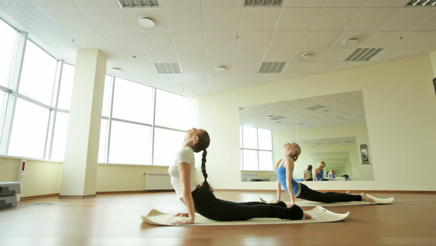 Girls in a gym keeping fit and flexible by doing exercises in a quick manner