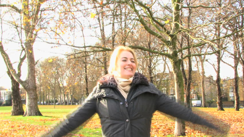 WIDE SHOT OF A YOUNG WOMAN STRETCHING IN A PARK - HD stock video clip