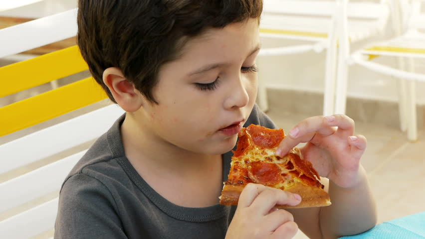 Boy Eating Pizza (HD). Six year old Hispanic boy eating a slice of pepperoni pizza.