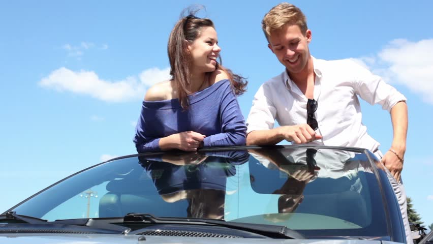 Young couple rest on front window of cabriolet and talk at sunny summer day - HD stock footage clip