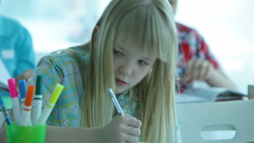 Close-up of a cute blond girl drawing in her exercise book, her classmates can be seen in the background - HD stock footage clip