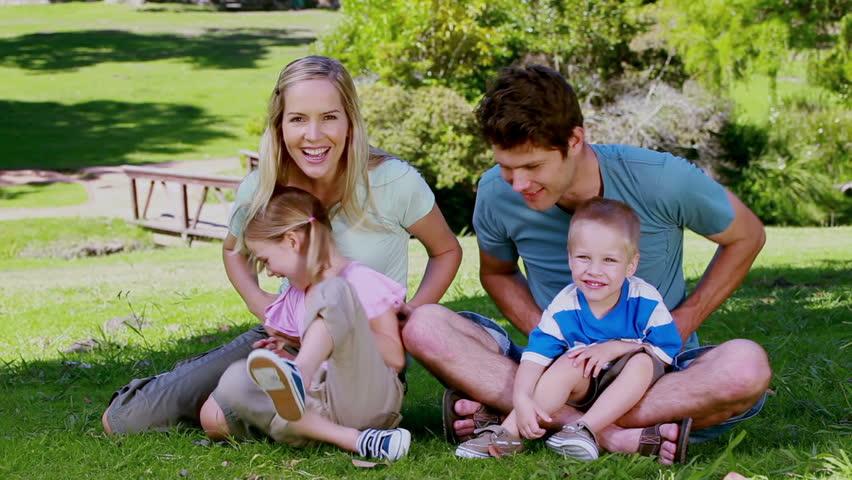 Parents tickling their children in a park