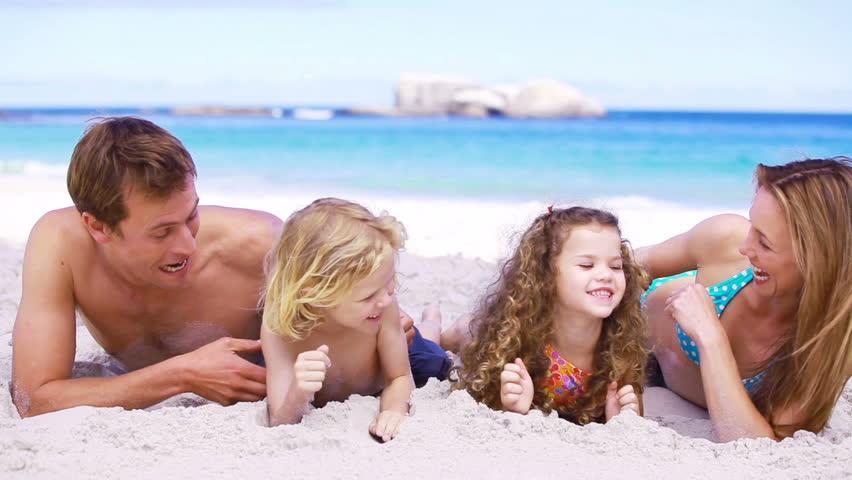 Happy parents tickling their children on the beach