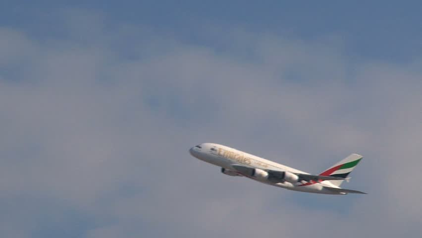 Dubai - Circa 2012: An Emirates airplane in 2012. An Emirates plane soaring over the city of Dubai, United Arab Emirates.