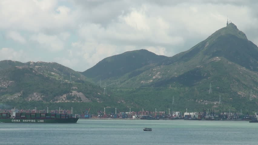 HONG KONG - JULY 28: An airplane lands at Hong Kong Airport, while a large cargo ship passes on July 28, 2010 in Hong Kong, China.