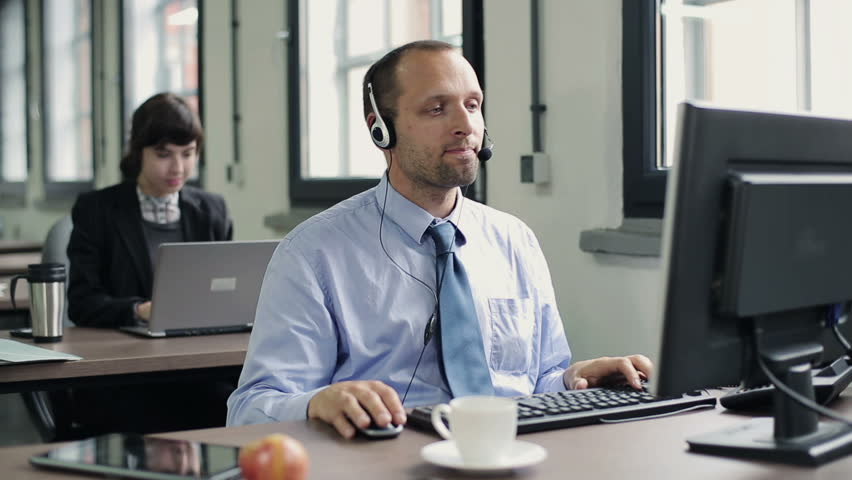 Friendly happy male helpdesk consultant in the office