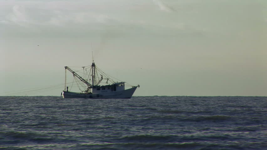 A fishing boat trawling for shrimp in the early evening light.  - HD stock footage clip