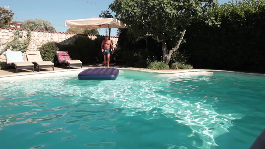 Funny Jump. Video of funny man jumping on water mat in the swimming pool.