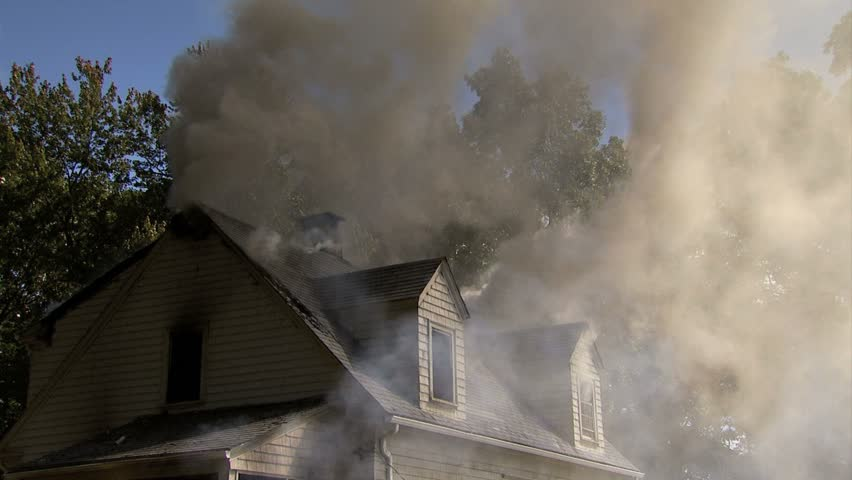 Lots of thick smoke pouring out from roof of house - medium shot