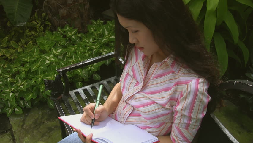 An attractive young asian woman writes, in a greenhouse. - HD stock footage clip