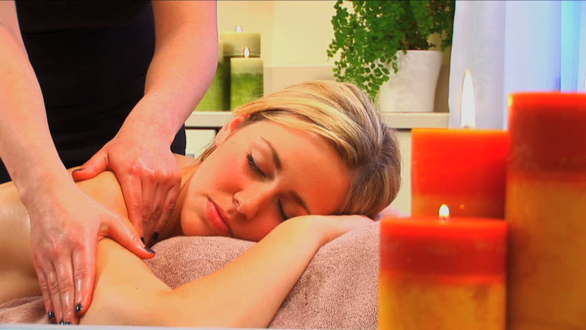 Beautiful blonde girl enjoys a massage at the health spa - HD stock footage clip