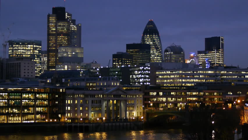 Skyline of the office towers of the City of London at night. Buildings include the Gerkin, Nat West Tower, Lloyds of London. The river Thames is visible at the bottom of the frame.