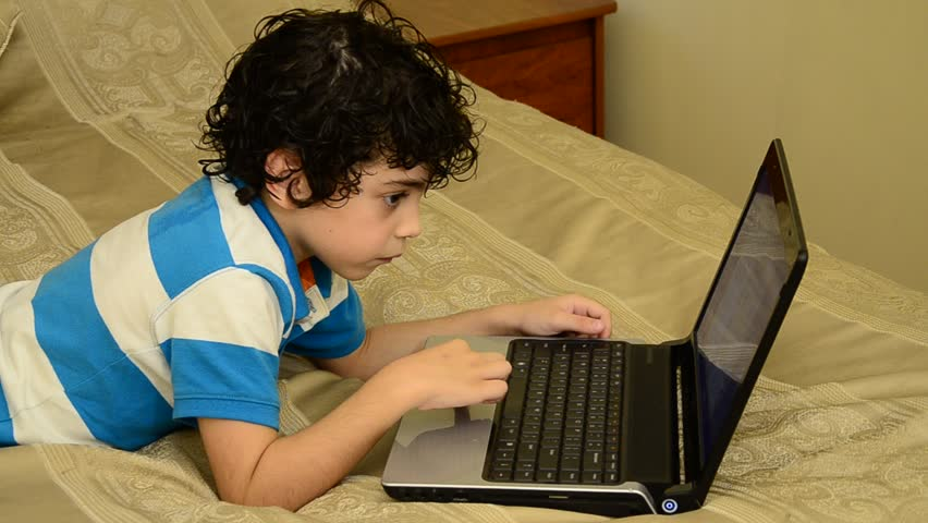 Young Latin boy playing e-games on a laptop at home
