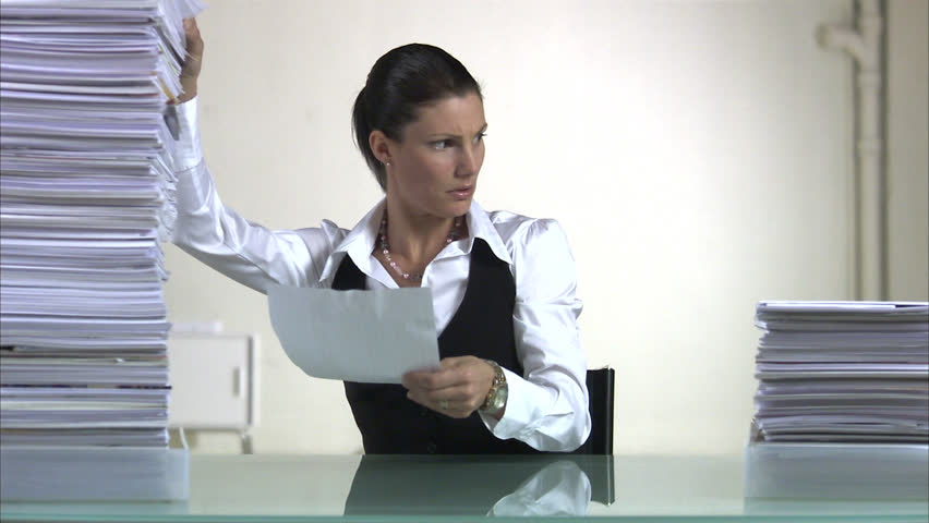 A woman ignoring an increasing pile of paper