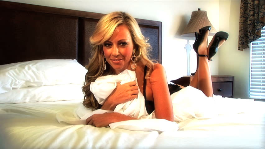 Sexy blonde girl relaxes on bed in hotel room - HD stock footage clip