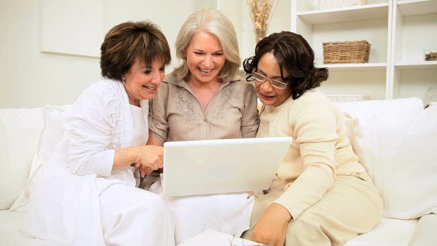 Three mature multi ethnic girlfriends home sofa enjoying online entertainment wireless laptop technology
