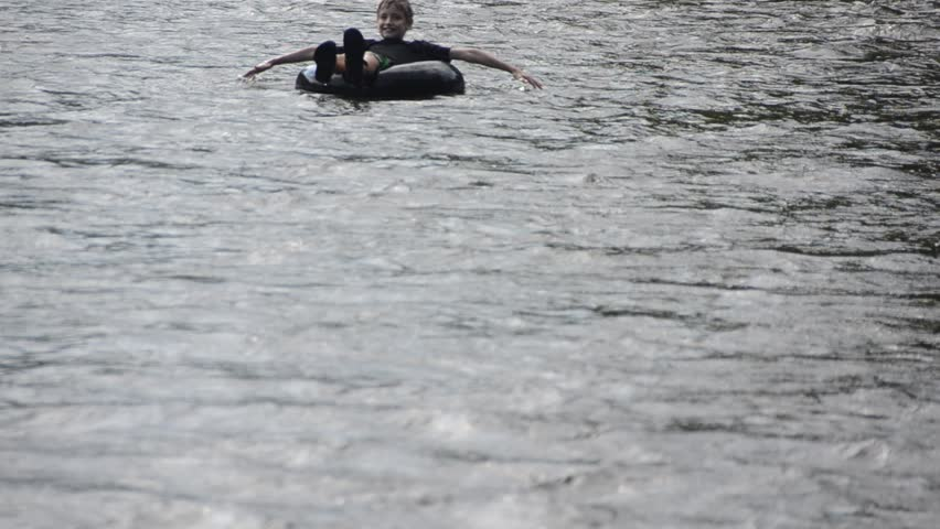 relaxed boy tubing on a calm river - HD stock video clip
