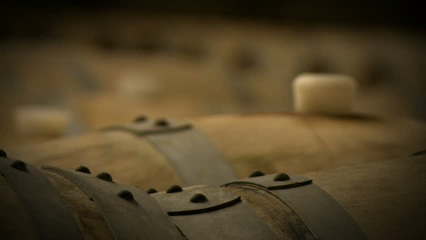 Rack focus along the tops of wine barrels, aging in the cellar of a winery.
