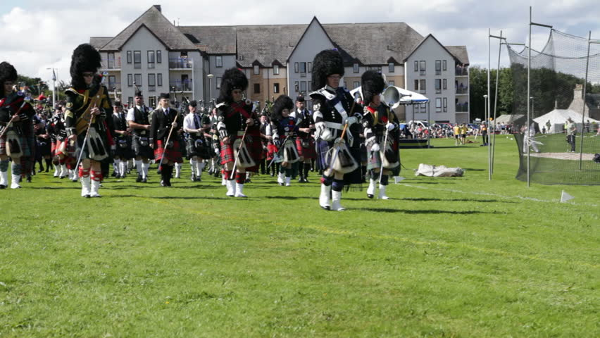 NAIRN, SCOTLAND - AUGUST 18: Massed pipe bands marching at the Highland Games in Nairn, Scotland on August 18, 2012. Highland games events are a popular tourist attraction during the Scottish summer. - HD stock video clip