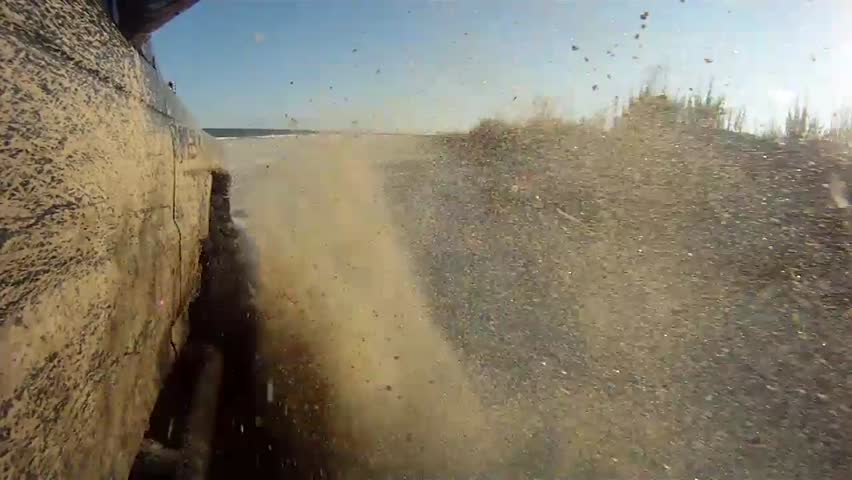 Off road driving in sand on a beach. Camera mounted at a low angle.