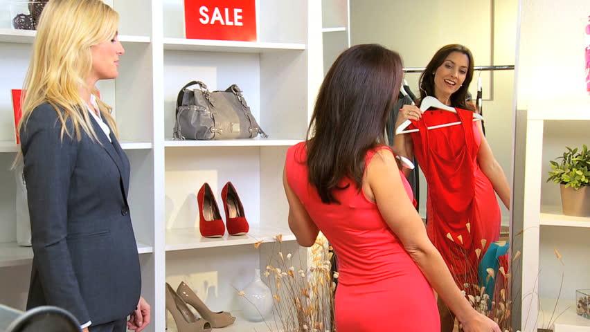 Smart brunette customer helped by female personal shopper in fashion boutique