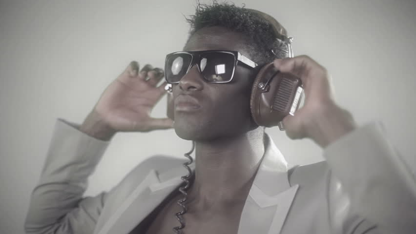 young african guy waving and dancing with a cool attitude with headphones and glasses