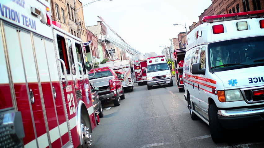 Emergency vehicles line the street at a 10-alarm fire on a small town's main street. - HD stock video clip