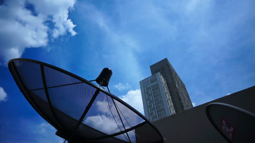 Black antenna communication satellite dish over sky in cityscape - time-lapse - HD stock footage clip