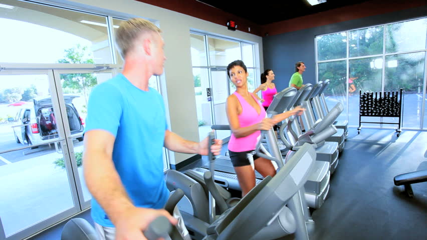 Gym members exercising on modern cross walker and treadmill equipment - HD stock video clip