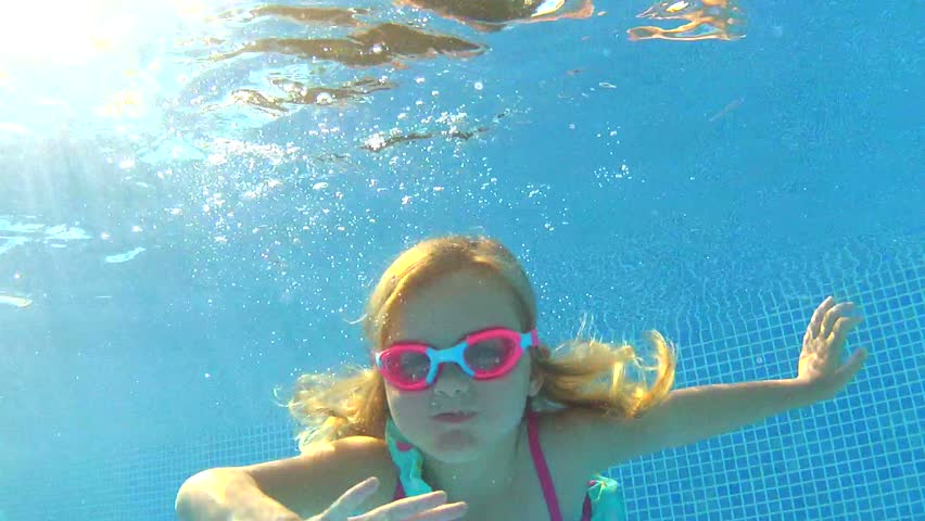 Underwater view young girl wearing goggles waving at camera.